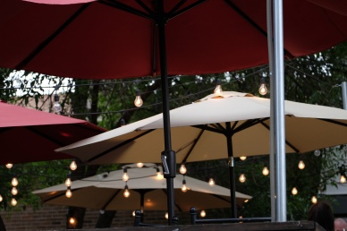 Patio umbrellas outside with lights on